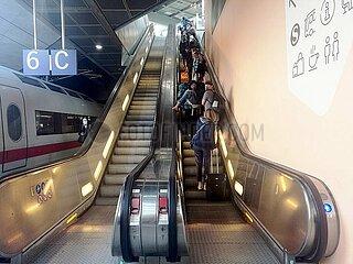 Menschen mit Schutzmasken auf einer Rolltreppe