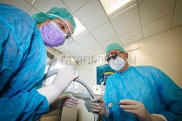 Zahnarzt und Zahnarzthelferin in besonderer Schutzkleidung