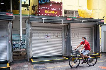Singapur  Republik Singapur  Radfahrer mit Mundschutz faehrt an geschlossenen Strassenstaenden in Chinatown vorbei
