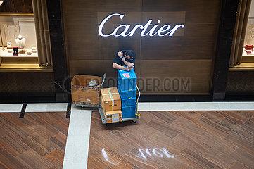 Singapur  Republik Singapur  Mann wartet in einem Einkaufszentrum vor Schmuckgeschaeft von Cartier