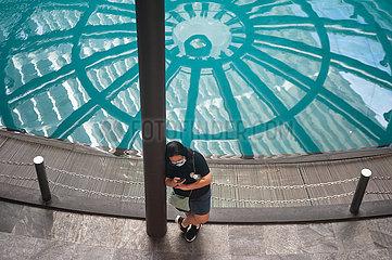 Singapur  Republik Singapur  Frau starrt neben Wasserbecken in einem Einkaufszentrum auf ihr Handy