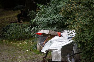 Deutschland  Frankfurt am Main - Obdachlose schuetzen sich in einem Park gegen den Regen