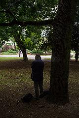 Deutschland  Frankfurt am Main - Obdachloser wartet unter einem Baum ab bis der Regen aufhoert