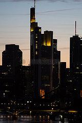 Deutschland  Frankfurt am Main - Skyline des Finanzviertels in der City in der Abenddaemmerung mit der Zentrale der Commerzbank AG  vorne der Main
