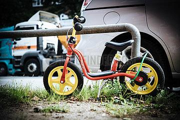 Puky Tretroller und Kinderfahrrad an Hauptverkehrstrasse