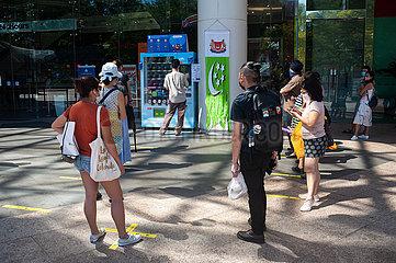 Singapur  Republik Singapur  Menschen mit Mundschutz vor einem Warenautomat mit wiederverwendbaren Schutzmasken