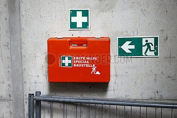 Symbolbild Arbeitssicherheit  Verbandskasten an einer Betonwand neben einem Schild Notausgang auf einer Baustelle  Nordrhein-Westfalen  Deutschland