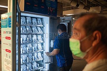 Singapur  Republik Singapur  Mann mit Mundschutz vor einem Warenautomat mit wiederverwendbaren Schutzmasken