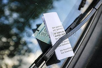 Ein Strafzettel klemmt an der Windschutzscheibe eines Autos auf einem Parkplatz  Essen  Nordrhein-Westfalen  Deutschland