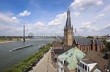 Rheinpromenade mit Lambertuskirche  hinten ein Frachtschiff auf dem Rhein und die Oberkasseler Bruecke  Duesseldorf  Nordrhein-Westfalen  Deutschland
