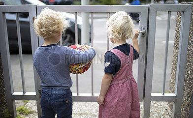 Kinder stehen an einem Toerchen