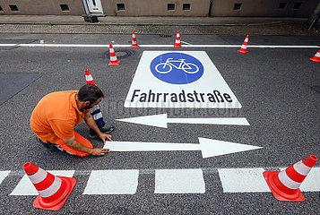 Neue Fahrradstrasse  ein Fahrbahnmarkierer beim Aufbringen der Fahrrad Piktogramme  Essen  Ruhrgebiet  Nordrhein-Westfalen  Deutschland