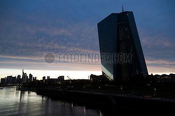 Deutschland  Frankfurt am Main - die Europaeische Zentralbank (EZB) bei dramatischer Beleuchtung im links der Fluss Main und die skyline des Bankenviertels in der City