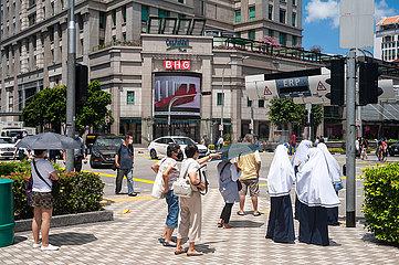 Singapur  Republik Singapur  Menschen warten an einer Fussgaengerampel im Stadtzentrum