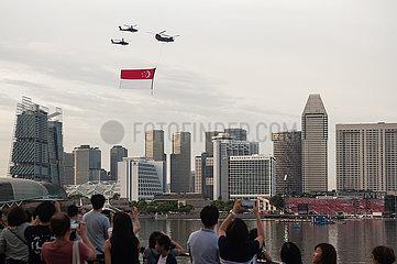 Singapur  Republik Singapur  Hubschrauber fliegen mit einer Staatsflagge ueber die Wolkenkratzer in Marina Bay