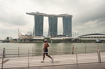 Singapur  Republik Singapur  Ein Jogger laeuft in Marina Bay ueber eine Bruecke