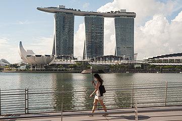 Singapur  Republik Singapur  Frau ueberquert eine Bruecke mit Marina Bay Sands Hotel im Hintergrund