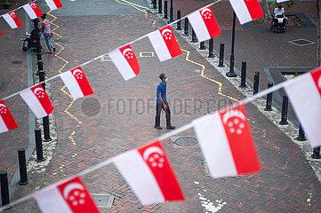 Singapur  Republik Singapur  Faehnchen in Nationalfarben als Wimpelketten haengen ueber einer Strasse