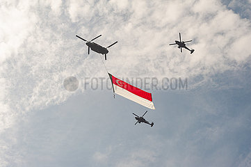 Singapur  Republik Singapur  Hubschrauber fliegen mit einer Staatsflagge ueber das Geschaeftsviertel in Marina Bay