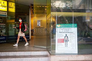 Singapur  Republik Singapur  Frau mit Mundschutz geht an einem Schild ueber das Coronavirus vorbei