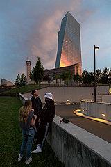 Deutschland  Frankfurt am Main - Jugendliche vor der Europaeischen Zentralbank (EZB) bei dramatischer Beleuchtung im Sonnenuntergang