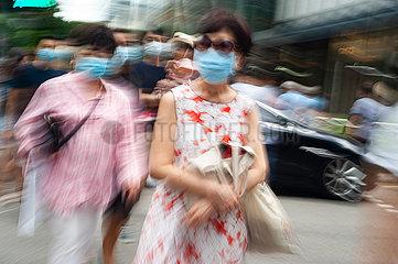Singapur  Republik Singapur  Fussgaenger mit Mundschutz gehen die Orchard Road entlang