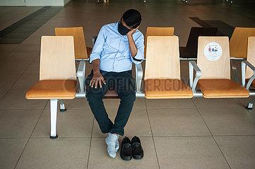 Singapur  Republik Singapur  Mann mit Mundschutz ruht sich im Terminal 1 am Flughafen Changi aus