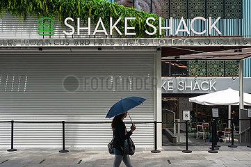 Singapur  Republik Singapur  Frau mit Mundschutz geht an einem neuen Shake Shack Restaurant vorbei