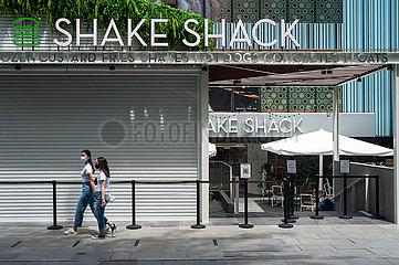 Singapur  Republik Singapur  Menschen mit Mundschutz gehen an einem neuen Shake Shack Restaurant vorbei