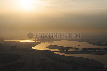 View from above on the Dubai Canal during sunrise with a thick layer of smog and air pollution