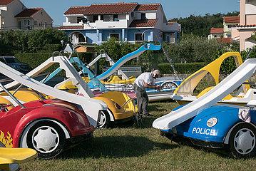 Kroatien  Rab  San Marino - Tretboote fuer Touristen an Land  Eigentuermer pflegt seine Boote
