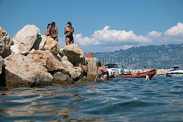 Kroatien  Rab  San Marino - Jugendliche kuehlen sich im Meer an der Einfahrt zum Hafen