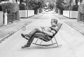 Mann im Schaukelstuhl auf der Strasse  Muenchen  August 2020