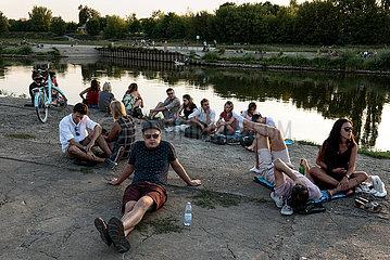 Polen  Poznan - Junge Leute am Rand eines Open-Air-Konzerts an der Warthe