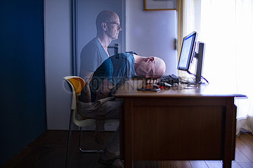 Mann sitzt zu Hause am Schreibtisch.