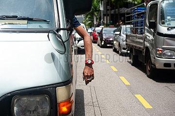 Singapur  Republik Singapur  Mann raucht eine Zigarette waehrend er im Berufsverkehr steht