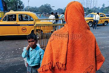 Kolkata (Kalkutta)  Indien  Person mit orangefarbenem Umhang und Kind vor gelben Taxis