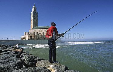 Casablanca  Marokko  Angler am Ufer vor der Hassan-II.-Moschee unter blauem Himmel
