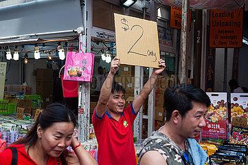 Singapur  Republik Singapur  Angebot auf Pappschild und Menschen auf einem belebten Basar in Chinatown