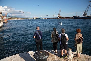 Kroatien  Rijeka - Menschen betrachten die Moewen am Hafen