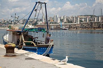 Kroatien  Rijeka - Fischer angelt im Hafen