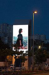 Kroatien  Rijeka - Riesiges LED-Display zeigt Werbung mit einer laechelnden  gehenden Frau