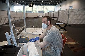 Deutschland  Bremen - Corona-Testzentrum in einer Messehalle  Medizinischer Fachangestellter nimmt Daten auf