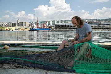 Kroatien  Rijeka - Fischer am Pier bessert Netze aus