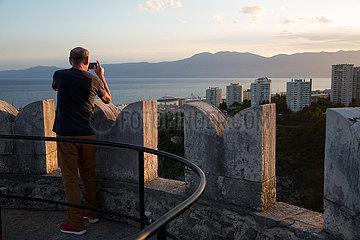 Kroatien  Rijeka - Tourist fotografiert vom Turm des Kastell von Trsat  eine historische  wieder aufgebaute Burg  Blick auf Innenstadt und Hafen