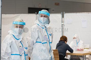 Deutschland  Bremen - Medizinische Fachangestellte Corona-Testzentrum in einer Messehalle erwarten zu testende Personen  hinten Eingangsgespraech mit Testperson