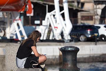 Kroatien  Rijeka - Maedchen sitzt am Hafen  beschaeftigt mit smartphone und social media