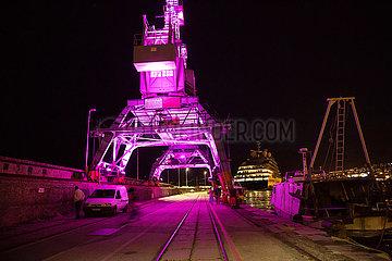 Kroatien  Rijeka - angeleuchtete Ladekraene auf dem Pier  rechts Fischerboot  hinten Megayacht