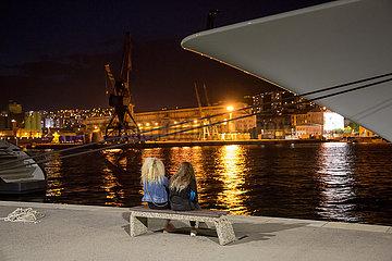 Kroatien  Rijeka - Zwei Maedchen sitzen auf einer Bank am Hafen
