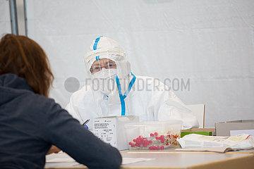 Deutschland  Bremen - Corona-Testzentrum in einer Messehalle  Aerztin bei Gespraech mit zu testender Person